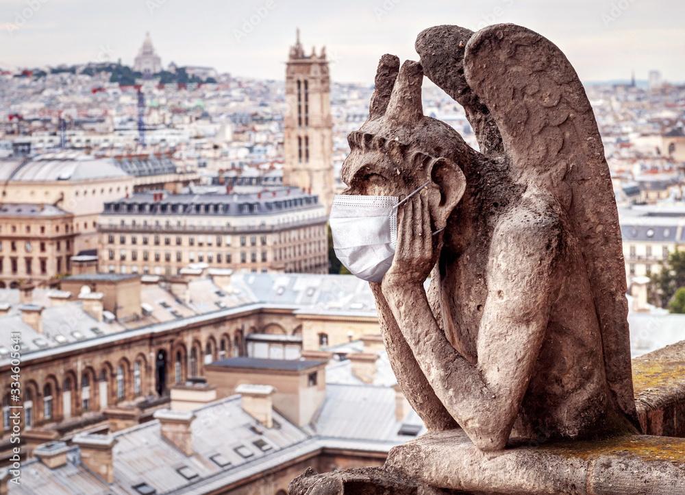 Fototapeta COVID-19 coronavirus in France, medical mask on gargoyle of Notre Dame in Paris. Tourist landmarks closed due to corona virus outbreak.