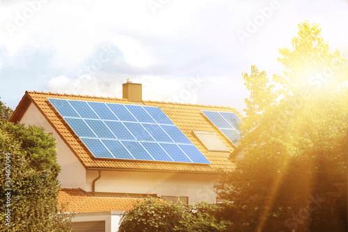 Obraz Solar panels on the tiled roof of the building in the sun. - fototapety do salonu