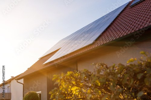 Photo Solar panels on the tiled roof of the building in the sun set.