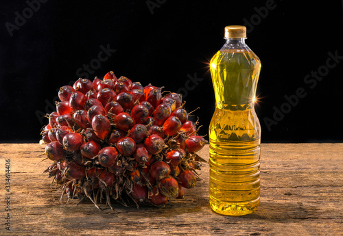 Fresh oil palm fruits and cooking palm oil on wooden background