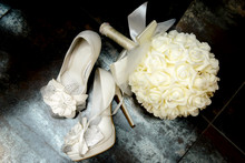 White Decorated Bridesmaid Shoes With A Wedding Bouquet On A Dark Background. End Of Banquet, Tired Bride
