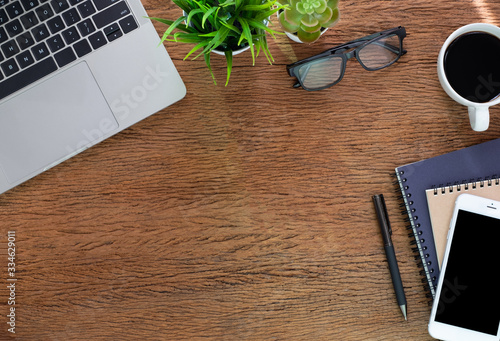 Fototapeta Workplace at home with wood table. Top view from above of laptop with notebook and coffee. Office space for modern creative work of designer. Flat lay with blank copy space. Business-finance concept. obraz na płótnie