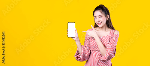 Fotografie, Tablou Portrait of Asian beautiful young woman hold smartphone and point finger on mobile phone with smile face