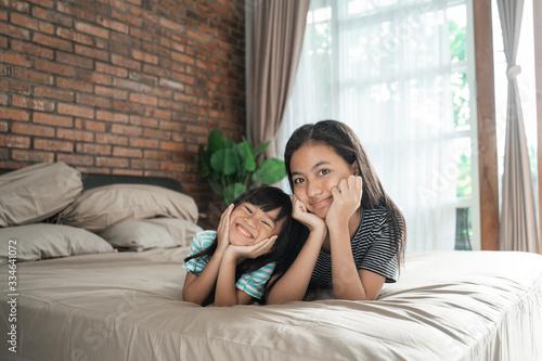 Fototapeta asian cute happy sibling sister smiling to camera obraz