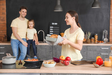 Young Family In Kitchen At Home