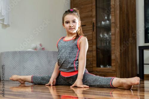 Fototapeta Trening domowy. Mała dziewczynka wykonuje ćwiczenia gimnastyczne na podłodze w salonie. obraz