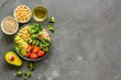Healthy salad bowl with quinoa, avocado and chickpeas on grey background top-down copy space