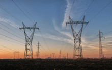 High-voltage Power Lines At Sunset, High Voltage Electric Transmission Tower. Industrial Concept.