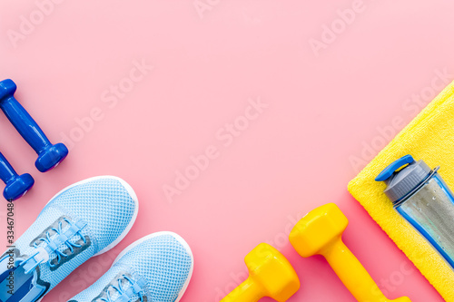 Fototapeta Athletics background with dumbbells, towel, sneakers on pink background top view copy space obraz