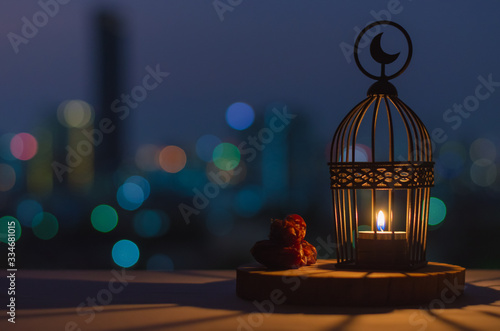 Fotomural Lantern that have moon symbol on top and dates fruit put on wooden tray with colorful city bokeh lights for the Muslim feast of the holy month of Ramadan Kareem