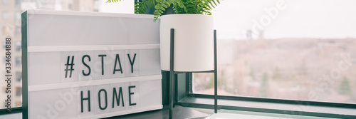 Fotografiet COVID-19 banner Coronavirus staying at home lightbox message sign with text hashtag #STAYHOME glowing in light to promote self isolation staying at home header background