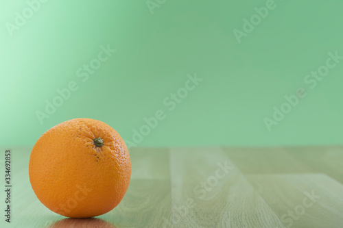 Orange fruit on table on the green wall background