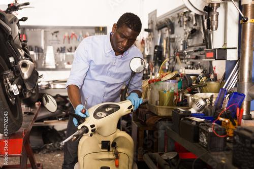 Male afro american worker repairing scooter in motorcycle workshop Wallpaper Mural