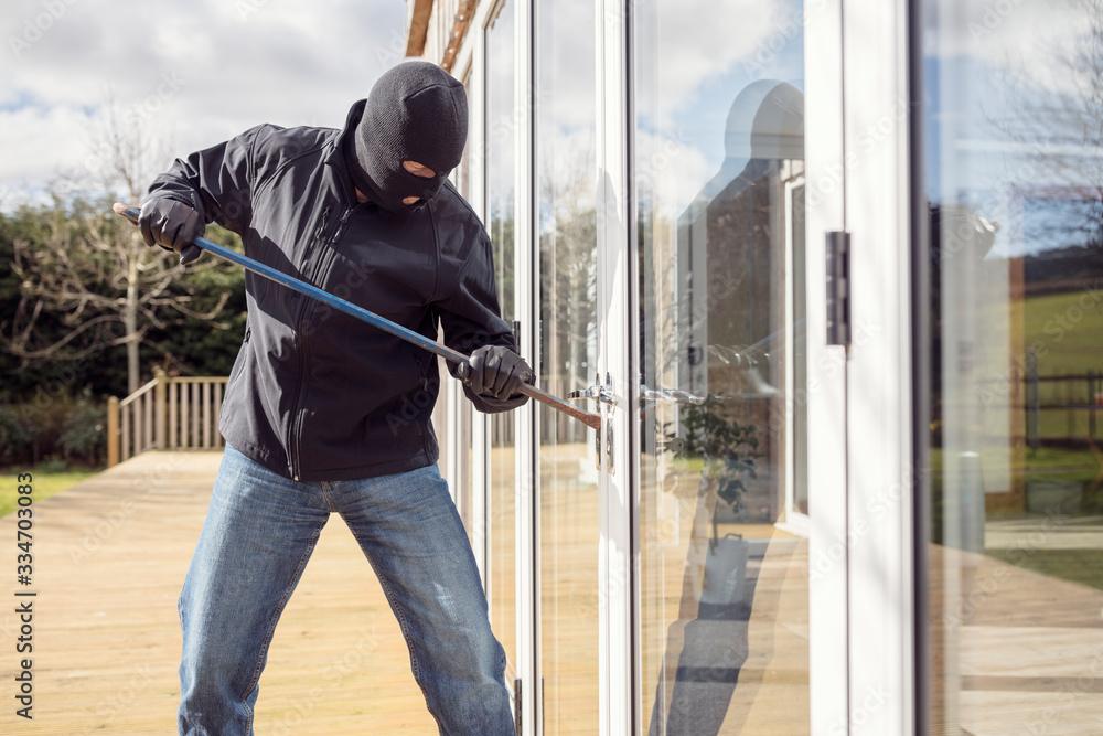 Fototapeta Burglar breaking into a house via a window with a crowbar