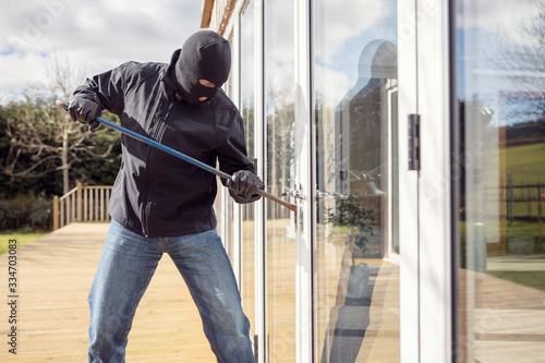Burglar breaking into a house via a window with a crowbar Canvas Print