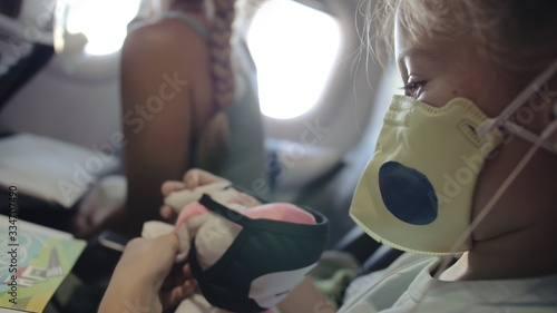 Fototapeta Little girl caucasian at plane with wearing protective medical mask. Child baby tourist at aircraft with respirator play and paint. Coronavirus epidemic sars-cov-2 covid-19 2019-ncov. obraz na płótnie