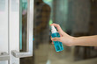 canvas print picture - woman is cleaning door handle with alcohol spray