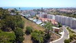 Aerial, orbit, drone shot of colorful villas and apartment buildings, in Amoreira, sunny day, in Estoril, Lisbon, Portugal