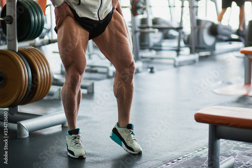 Cuadros en Lienzo Male muscular athlete bodybuilder show thigh muscles.