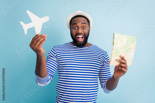 Photo of excited dark skin guy traveler hold paper air plane map offer nice cheap travel variants low prices wear white sun cap striped sailor shirt isolated blue color background