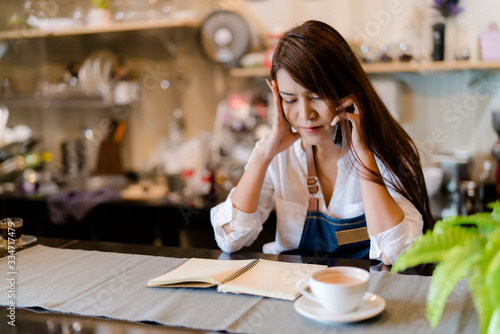 Valokuvatapetti An Asian barista woman is stressed because of economic conditions and COVID-19 o