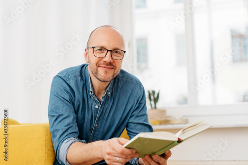 Fotografie, Obraz Happy friendly man wearing glasses with a book