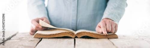 Fotografia hands praying with a bible over wooden table