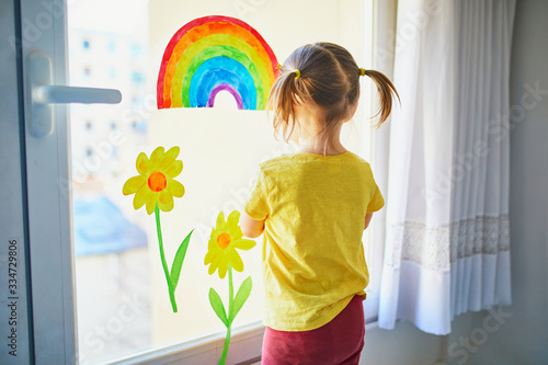 Adorable toddler girl attaching drawing of rainbow to window glass as sign of ho Fototapet