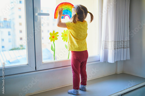Adorable toddler girl attaching drawing of rainbow to window glass as sign of hope