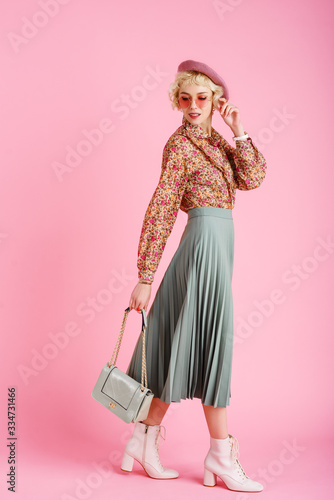 Full-length studio fashion portrait of young elegant happy smiling woman wearing trendy spring outfit: floral print blouse, green pleated skirt, white ankle boots, holding stylish  faux leather bag Wall mural