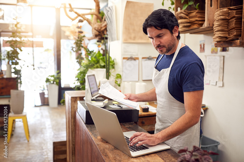 Photo Male Sales Assistant Working On Laptop Behind Sales Desk Of Florists Store