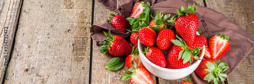 Fotografija Heap of fresh organic strawberries in ceramic bowl on rustic wooden background?