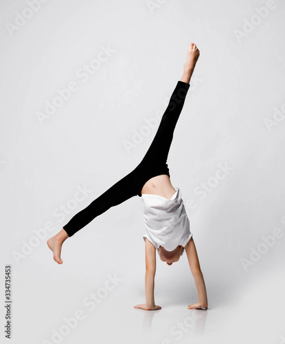 Fototapeta Athletic kid girl is doing gymnastic acrobatics exercises at home in studio, handstand and stretching with her legs up obraz