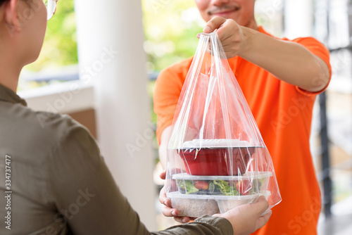 Fototapeta Delivery man giving lunch box meal in the bag to customer that ordered online at home obraz