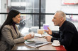 side view of businessman and smiling asian businesswoman talking in cafe