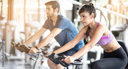 Foto Young asian healthy woman bike cardio at the gym with smile and fresh face with her friend