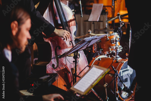Photo Concert view of a contrabass violoncello player with vocalist and musical during