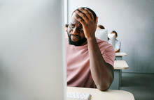 Upset, Sad Man Is Sitting At Computer. Job Search, Crisis, Unstable Situation In The World.