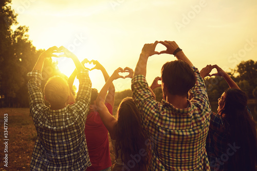 Fotografía Heart sign with hands of a group of people at sunset.