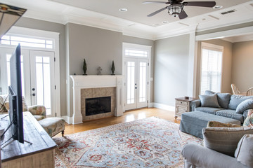 a bright and airy neutral beige living room den in a new construction house with a white and tiled fireplace as the main focal point as well as a decorative rug and lots of natural window light.