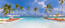 Outdoor Tourism Landscape. Luxurious Beach Resort With Swimming Pool And Beach Chairs Or Loungers Under Umbrellas With Palm Trees And Blue Sky. Summer Travel And Vacation Background Concept