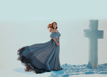 Young Sad Woman Princess. Backdrop Blue Sky White Snow Winter. Snowy Frosty Desert Ice Cross. Religion Concept Spirituality Pray With Hope. Red Hair Flying In Wind. Medieval Vintage Dress Fluttering