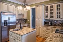 A Square Shaped Green Kitchen With Cream Colored Cabinets In A New Construction Home With Granite Countertops And Lots Of Cabinets And Storage Space
