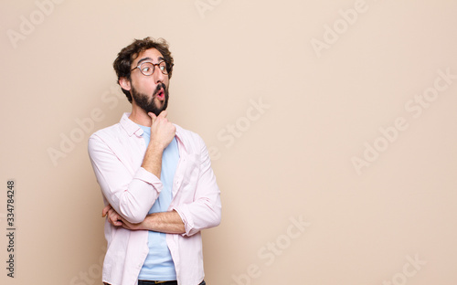 Fotografiet young bearded man expressing a concept against flat wall