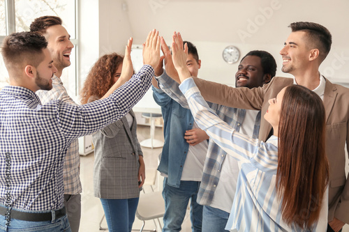Photo Group of people putting hands together indoors. Unity concept