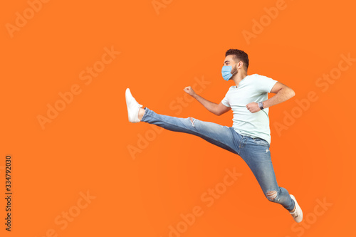 Full length portrait of excited man with surgical medical mask in casual style jumping over in air, running quickly fast, in hurry for discounts Canvas-taulu