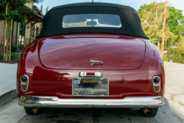 Classic 1951 Simca 8 Sport convertible car looks pretty from rear view with roof top up.