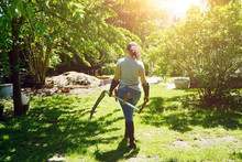 Woman At Gardening In The Garden Mows Wild Meadow With Scythe On A Sunny Summer Day