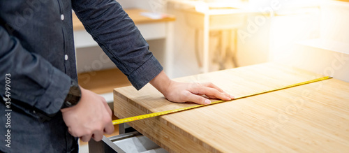 Male hand interior designer using tape measure for measuring size of wooden countertop in modern kitchen showroom in furniture store Fototapet