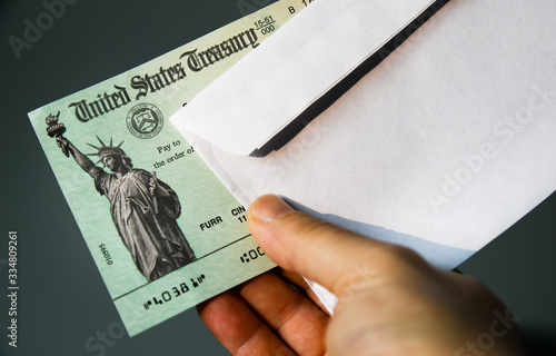 Obraz United States Treasury check surrounded by US currency.  Illustration for stimulus package checks expected to ease the impact of Corona Virus (Covid-19) restrictions or IRS income tax refund. - fototapety do salonu